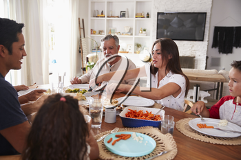 Millennial woman serving her relatives at a three generation Hispanic family meal