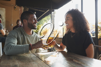 Young Couple Meeting In Sports Bar Enjoying Drink Before Game