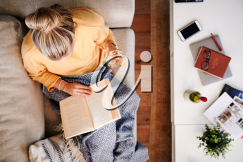 Overhead Shot Looking Down On Woman At Home Lying On Reading Book And Drinking Wine