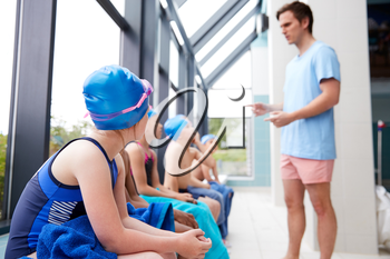 Male Coach Giving Children In Swimming Class Briefing As They Sit On Edge Of Indoor Pool