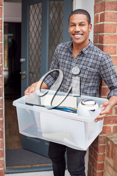 Portrait Of Male College Student Carrying Box Moving Into Accommodation