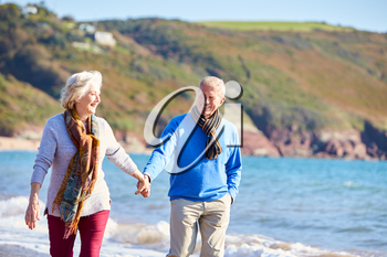 Loving Senior Couple Holding Hands As They Walk Along Shoreline Of Beach By Waves