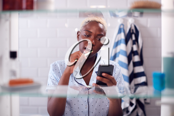 View Through Bathroom Cabinet Of Woman Brushing Teeth And Checking Phone Before Going To Work