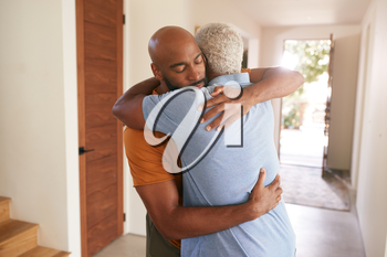 Loving Senior Father Hugging Adult Son Indoors At Home
