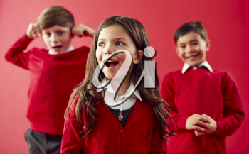 Group Of Excited Elementary School Pupils Wearing Uniform Having Fun Against Red Studio Background