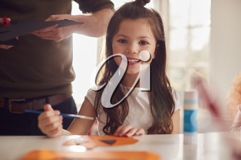 Portrait Of Daughter At Home With Father Having Fun Making Craft Together