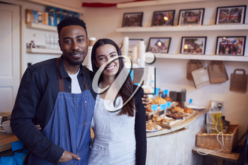 Portrait Of Smiling Couple Running Coffee Shop Together Standing Behind Counter