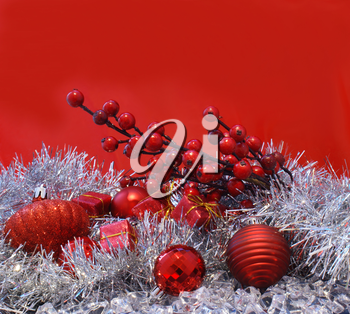 Christmas berries, baubles and gifts on a red background