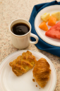 Royalty Free Photo of Continental Breakfast of Coffee, Pastry, and Fresh Fruit