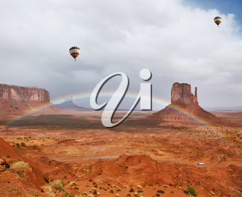 Balloons under storm clouds. Monument Valley - Navajo Reservation during the summer thunderstorms. The magnificent rainbow over the famous red sandstone Mittens
