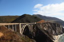 Huge viaduct on mountain road on Pacific coast USA. Bright serene autumn day