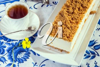 Gorgeous white cheesecake, sprinkled with sweet crumbs. Professional bakery. The background is  porcelain cup with hot tea