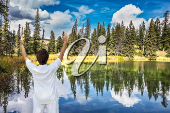 Jasper National Park in the Rocky Mountains of Canada. Patricia Lake. Middle-aged woman, dressed for yoga, Sun Salutation on the shore of small lake
