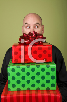 Royalty Free Photo of a Man Holding a Pile of Presents