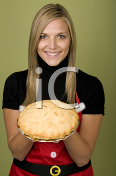 Royalty Free Photo of a Woman in a Christmas Apron Holding a Pie