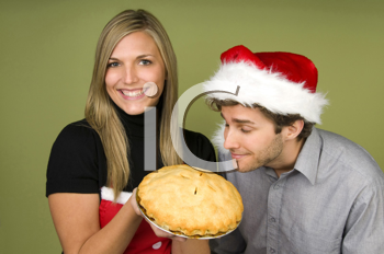 Royalty Free Photo of a Man in a Santa Hat Smelling Pie Held by a Woman