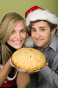 Royalty Free Photo of a Couple Holding a Pie and the Man's in a Santa Hat