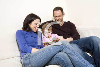 Royalty Free Photo of a Couple Reading To Their Child