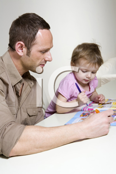 Royalty Free Photo of a Father Helping His Daughter Colour