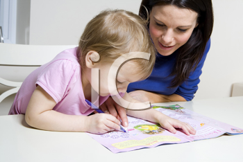 Royalty Free Photo of a Woman Helping Her Child With an Activity Book