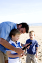 Royalty Free Photo of a Father and Sons Flying a Kite on the Beach
