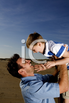 Royalty Free Photo of a Man Lifting His Child in the Air