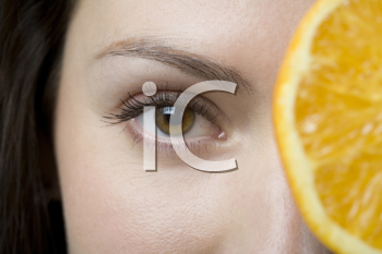 Royalty Free Photo of a Woman With an Orange Slice Over Her Eye