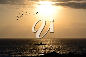 Silhouette of fishermen with his boat alone in the ocean