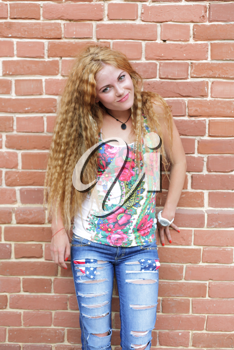 Beautiful woman with long blond hair standing against brick-wall
