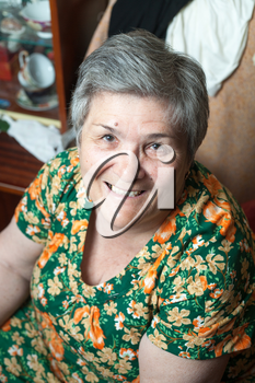 Closeup portrait of senior womanin chair, looking at camera, smiling.