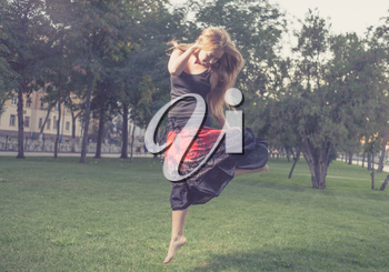 The young female jumps on a green grass in evening time in city park . Girl jumping like flying bird.