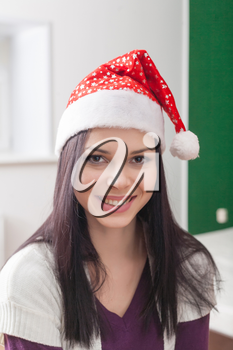 smiling brunette in  santa hat, vertical indoor shot