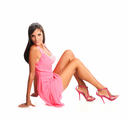 Portrait of beautiful dark haired model in pink dress siiting on the floor in studio on white