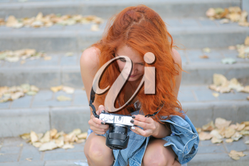 Young redhead woman photographer. Cute women halding modern camera in her hands and looking at screen inspect images