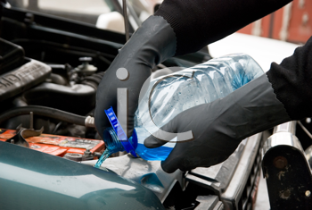 Royalty Free Photo of a Mechanic Filling a Car With Washing Liquid