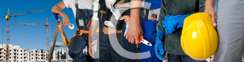 Royalty Free Photo of Workers Holding Tools With a Building in the Background