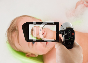 Royalty Free Photo of a Woman Recording Her Baby Taking a Bath