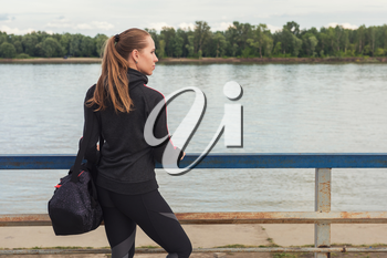 A woman in sportswear with bottle of water on embankment background