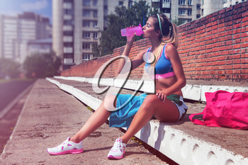 A young beauty athletic woman in sportswear warming-up before exercises and running.