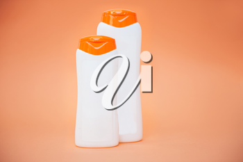 Different cosmetic bottles of cream, soaps, foams or shampoo on orange background.