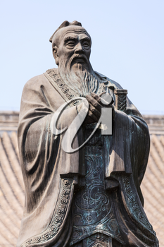 Bronze statue of Confucius, chinese teacher and philosopher against blue sky