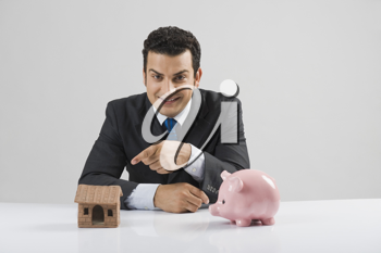 Businessman with a model home and a piggy bank