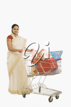 Woman carrying gifts in a shopping cart