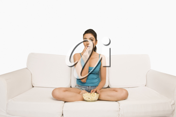 Woman sitting on a couch and eating popcorn