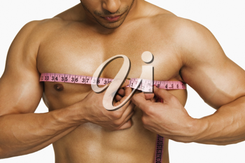 Close-up of a man measuring his chest with a tape measure