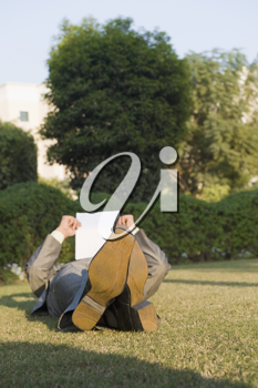 Businessman lying and reading a paper in a park