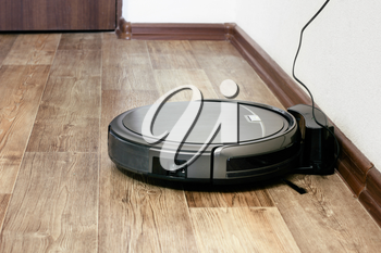 robot vacuum cleaner on the parquet floor in the apartment