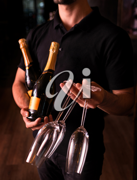 Man holding Champagne and glasses on dark background
