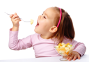 Royalty Free Photo of a Little Girl Eating Fruit Salad