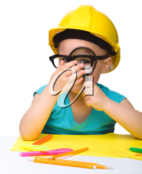 Royalty Free Photo of a Little Girl Wearing a Hardhat Looking Through a Magnifying Glass